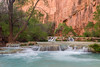 The blue water of Havasu Creek flows in the beautiful canyon walls it carved out to make a canyon.
